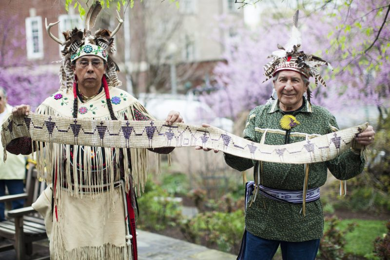 Two indigenous males standing in traditional clothing holding a long wampum beaded work in their hands