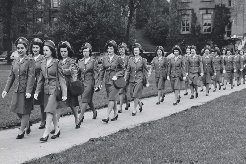 women in uniform walking in unison on campus