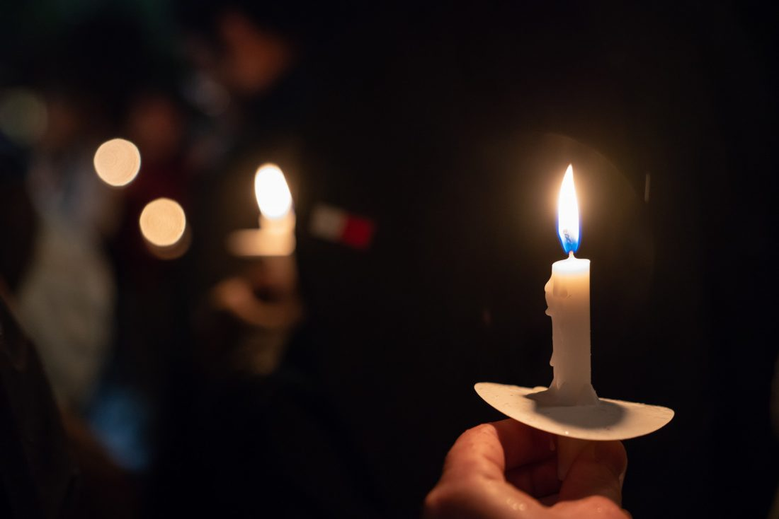Holding one small lighted candle
