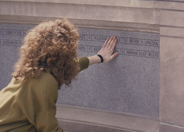 women placing hand on Pan Am memorial wall in front of Hall of Languages