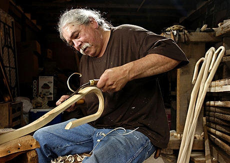 Man with gray hair pulled back, wearing blue jean pants, a black long sleeved shirt. Sitting on a chair, carving a rounded wooden stick
