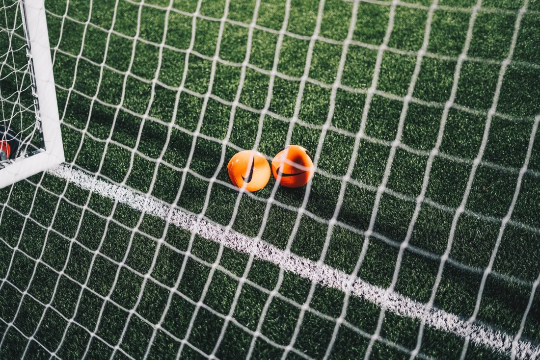 Two orange soccer balls resting under a goal.