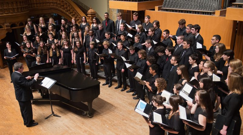University concert choir and singers performing onstage.