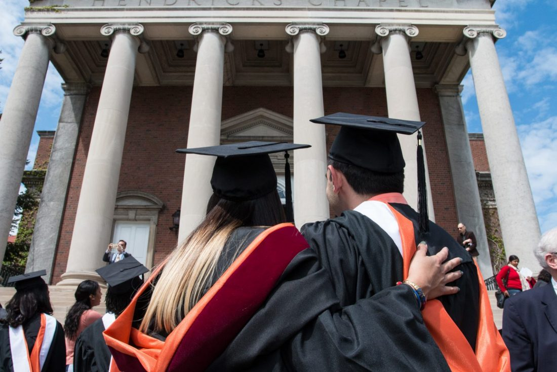 Students in graduation attire in front of Hendricks Chapel