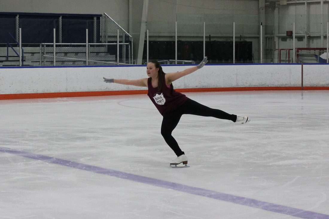A figure skater wearing a sleeveless shirt lands a jump on one skate with her arms outstretched.