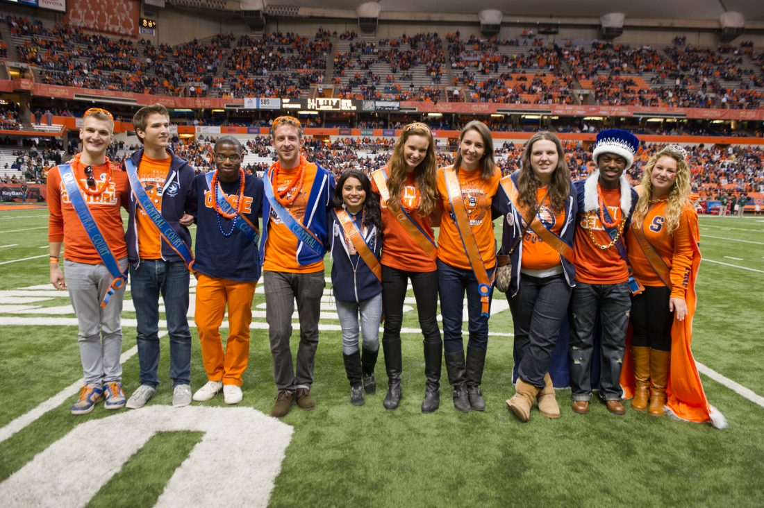 Members of Homecoming Court stand next to each other on Dome turf wearing their Homecoming Court sashes.
