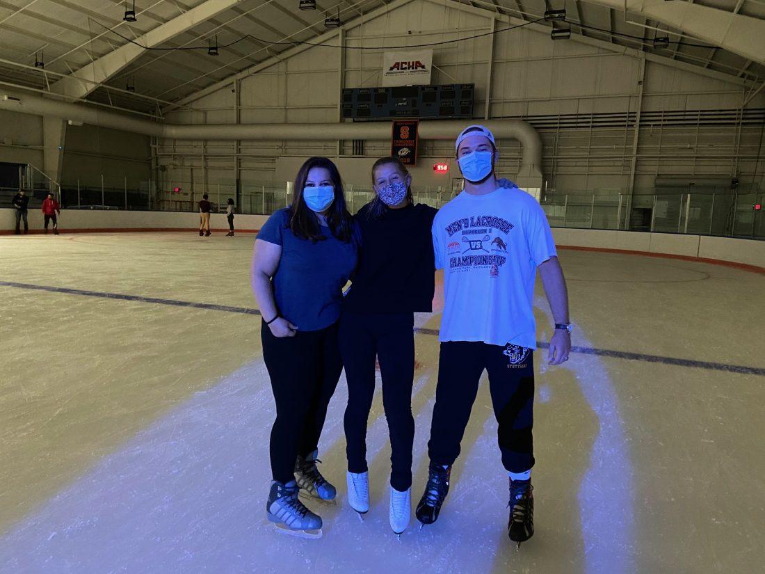 Three students ice skating at Late Night Ice.