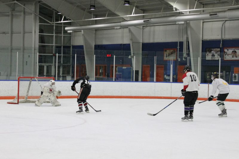 A hockey player attempts to score on a breakaway.