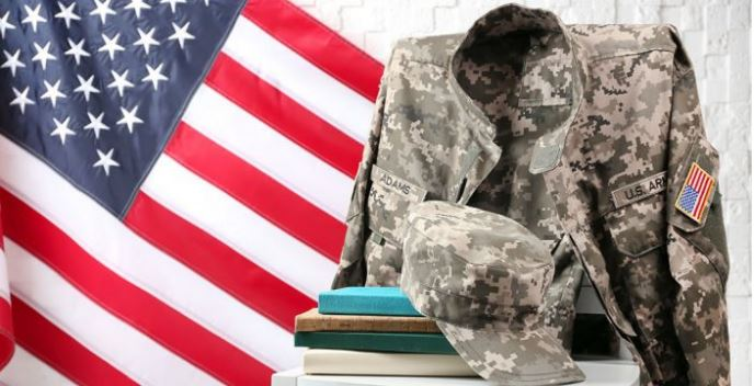 Visual of a stack of books and military uniform in front of an American flag backdrop