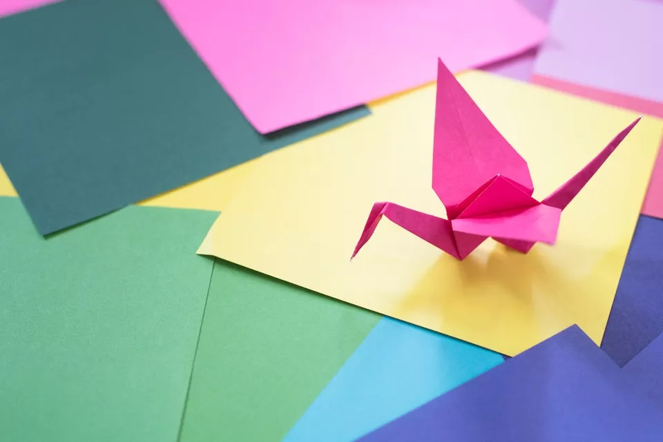 Numerous sheets of paper of various colors including blue, yellow, greens and pink covering a table surface with a pink origami crane on top of a yellow sheet