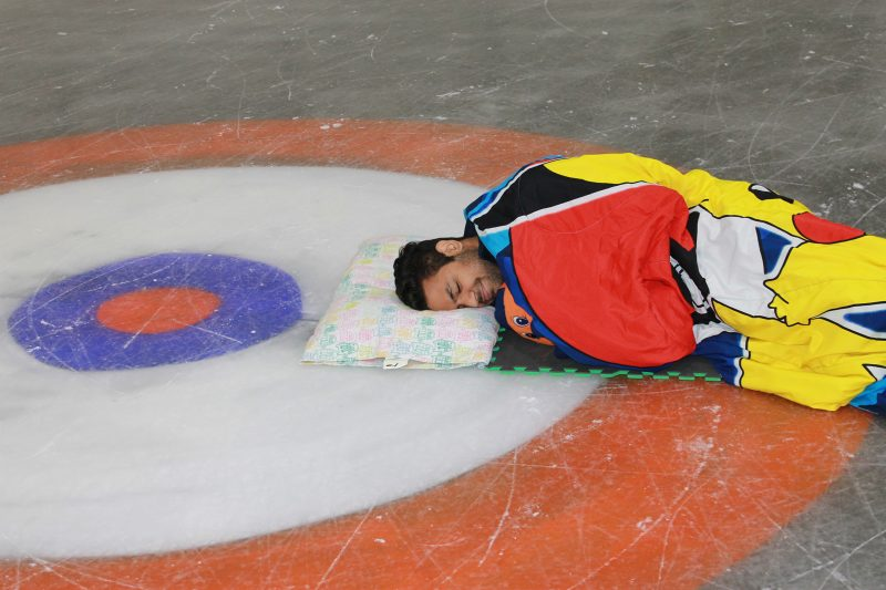 A student naps on the ice awaiting the Pajama Jam.