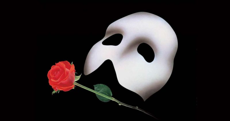 White mask and rose on black background
