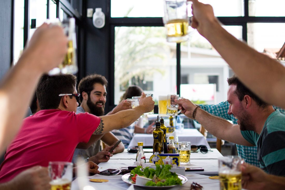 People cheering with drinks in restaurant