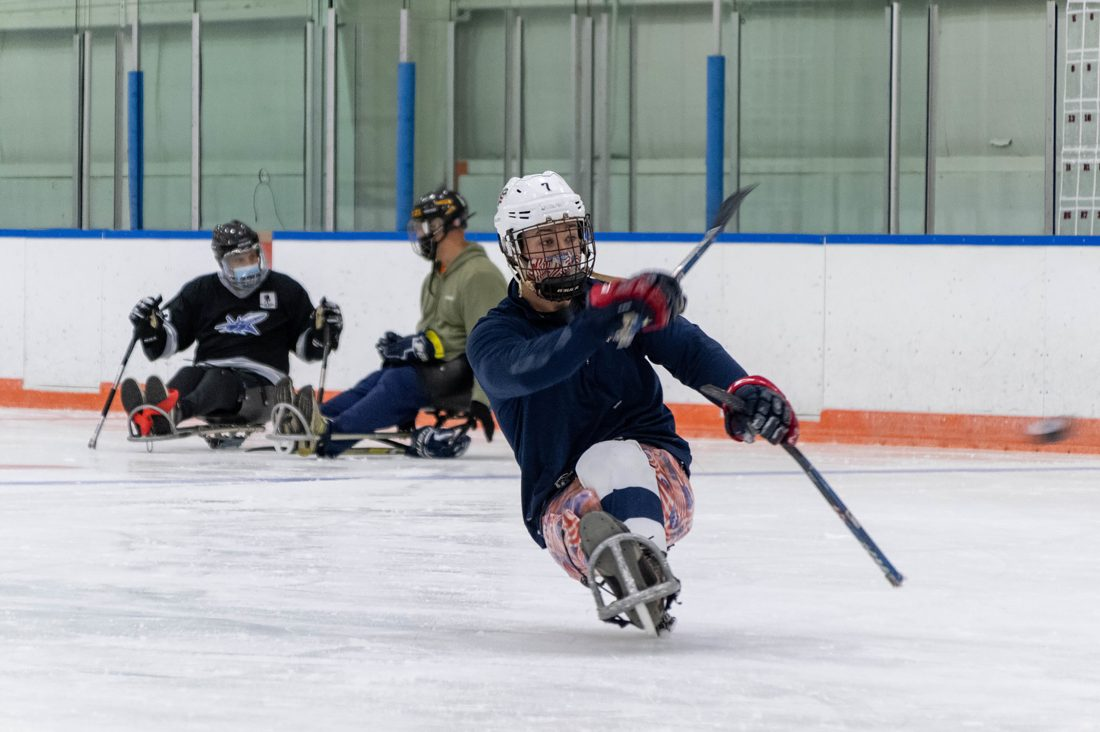 A hockey player in an adaptive sled shoots the puck.