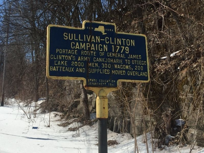 Sullivan-Clinton Campaign 1779 highway marker in New York State. Blue sign with a gold border on the side of the highway in the snow. Image by Steve Stoessel, hmdb.org
