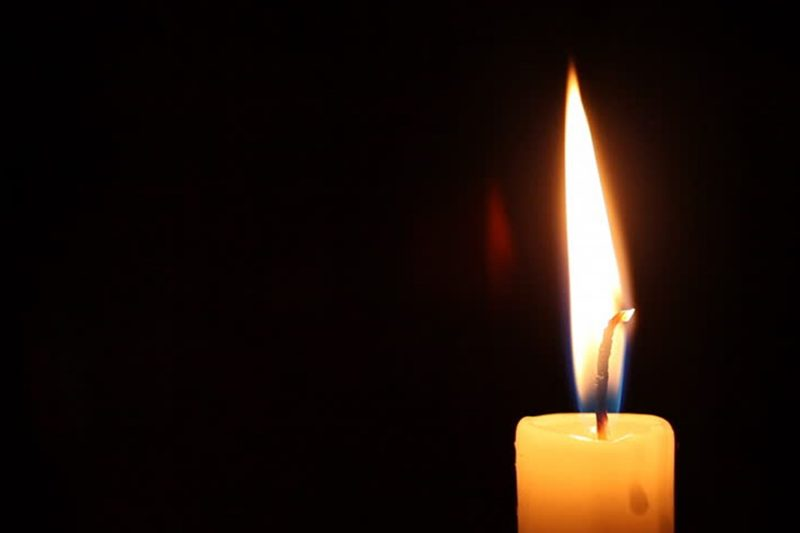A lit candle against a black background