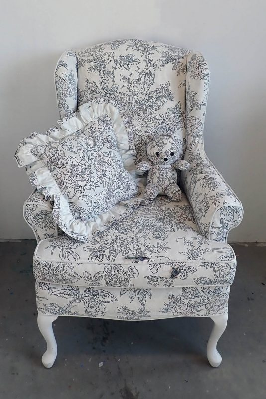 Armchair with a white background with hand drawn black designs. A decorative pillow and a small teddy bear in the same design is perched on the chair