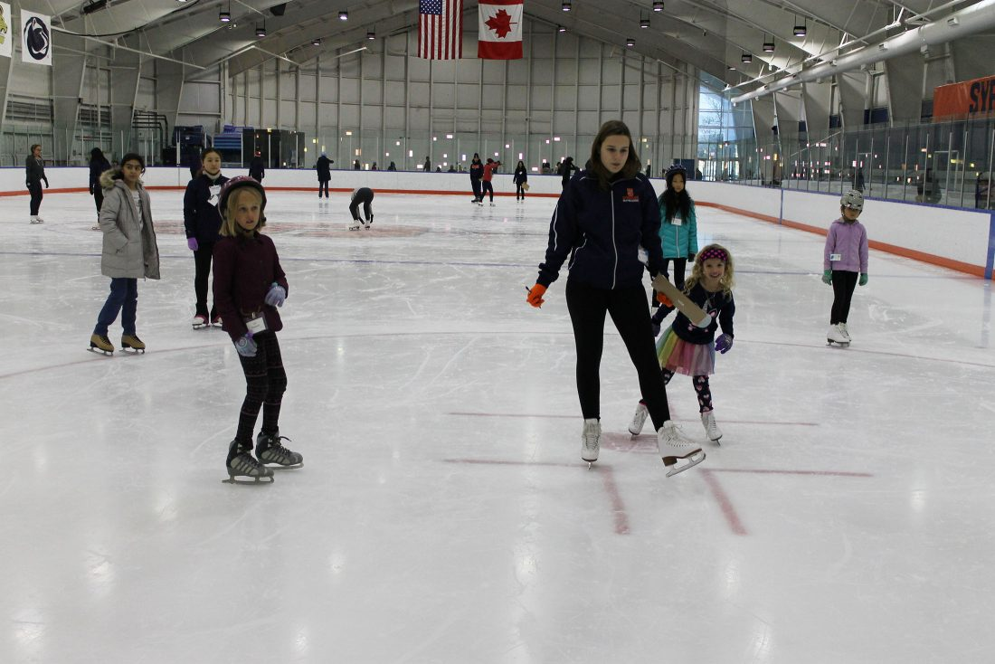 Children participate in a group skating lesson.