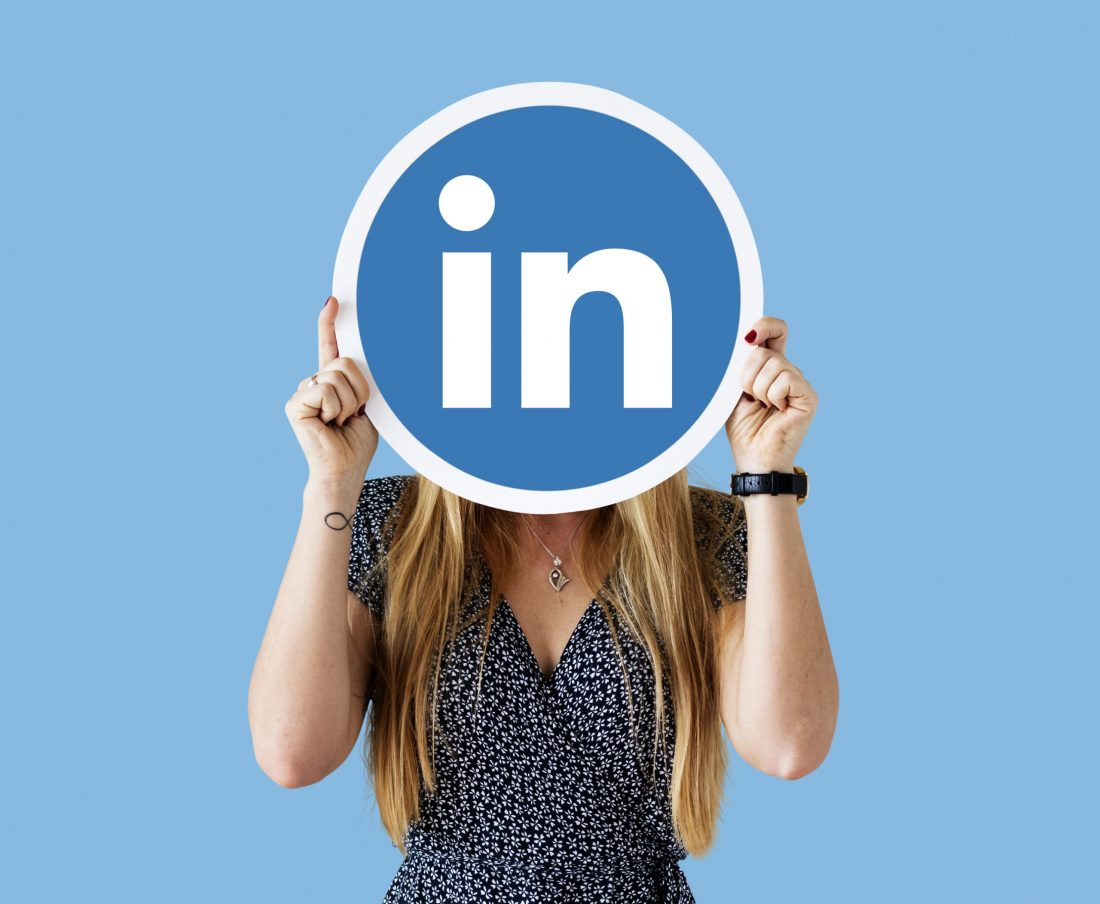 Woman holding circle of LInkedIn logo in front of her face